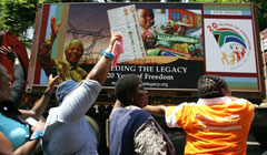 People cheering on the trucks of the 20 Years of Freedom exhibition as it drives by in Pretoria